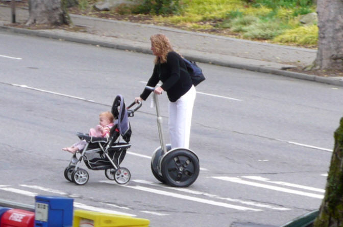 Woman pushing child on Segway