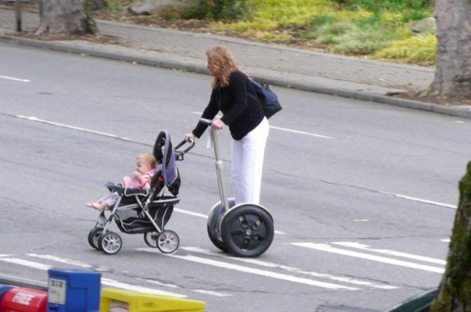 Woman pushing child on Segway