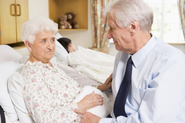 Senior Man Sitting With His Wife In Hospital
