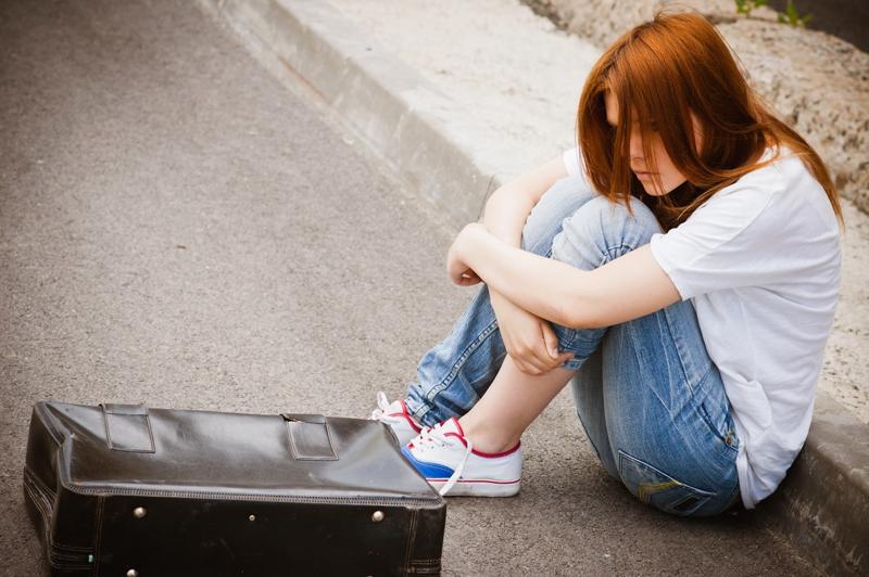 Beautiful young sad girl sitting on asphalt